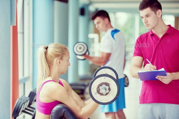 young sporty woman with trainer exercise weights lifting - Stock Photo - Images
