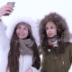 Beautiful Girls Making Selfies on Cell Phone and Watching Photos during Snowfall - VideoHive Item for Sale