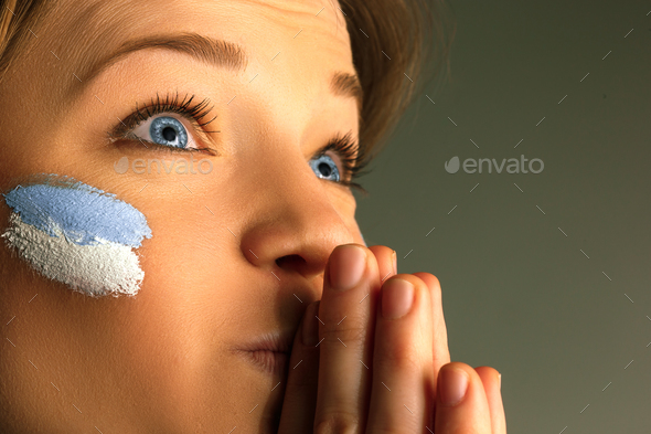 Portrait of a woman with the flag of the Argentina painted on her face. - Stock Photo - Images