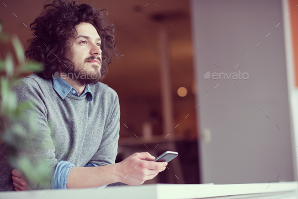 Young casual businessman holding smartphone - Stock Photo - Images