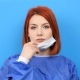 Redhead Woman Wearing a Surgeon Robe Puts Her Mask on - VideoHive Item for Sale