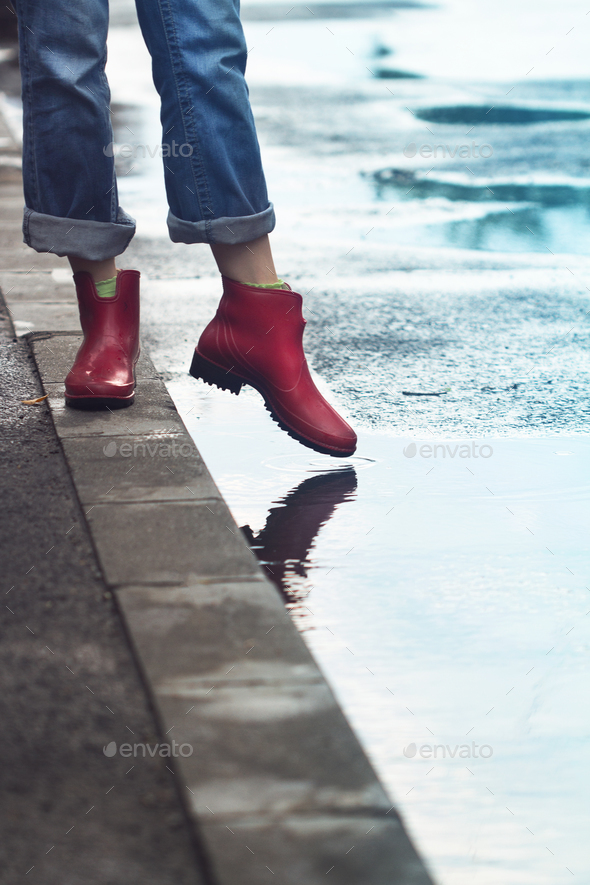 woman with red short boots standing on sidewalk next to a puddle - Stock Photo - Images