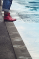 woman with red short boots standing on sidewalk next to a puddle - PhotoDune Item for Sale