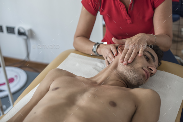 physiotherapist visits a young sportsman who feels pain at shoulder - Stock Photo - Images