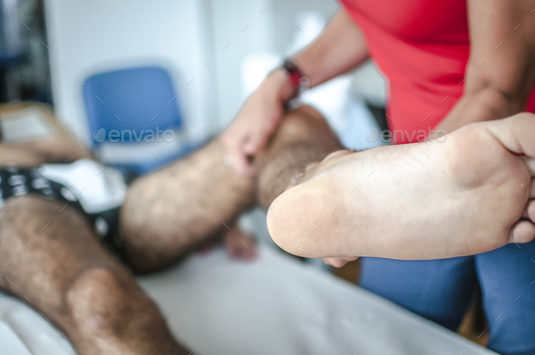physiotherapist visits a young sportsman who feels pain at leg - Stock Photo - Images