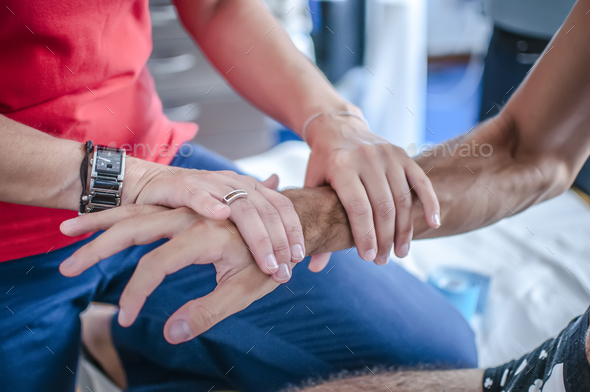 physiotherapist applying tape after massage for pain to a sports young - Stock Photo - Images