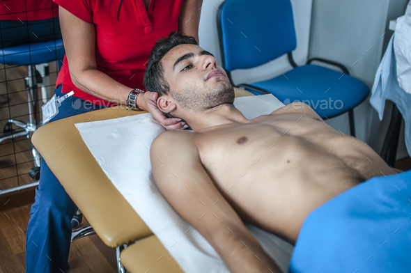 physiotherapist visits a young sportsman who feels pain at the back - Stock Photo - Images