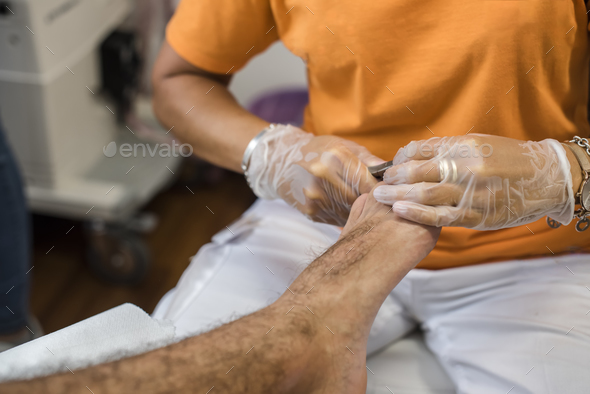 podiatry doctor curing an elderly patient feet - Stock Photo - Images