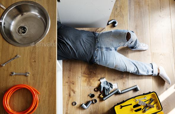 Plumber man fixing kitchen sink - Stock Photo - Images