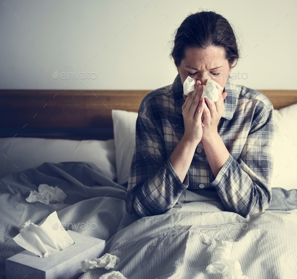 A woman suffering from flu in bed - Stock Photo - Images