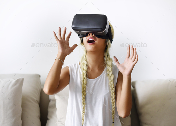 A young woman trying on VR headset - Stock Photo - Images