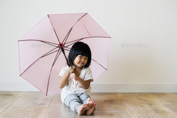 Young Asian girl playing alone - Stock Photo - Images