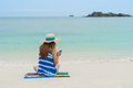 Young woman relaxing and using mobile phone at the tropical beach - PhotoDune Item for Sale