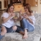 Two Girls Eat Salad Sitting on the Couch. - VideoHive Item for Sale