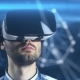 A Young Man with a Beard in Glasses of Virtual Reality on a Technological Background - VideoHive Item for Sale