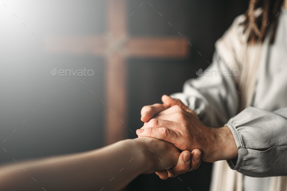 Jesus Christ gives a helping hand to the faithful - Stock Photo - Images