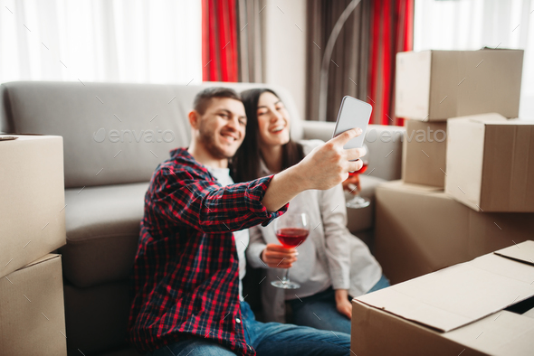 Couple makes selfie against boxes, moving to house - Stock Photo - Images
