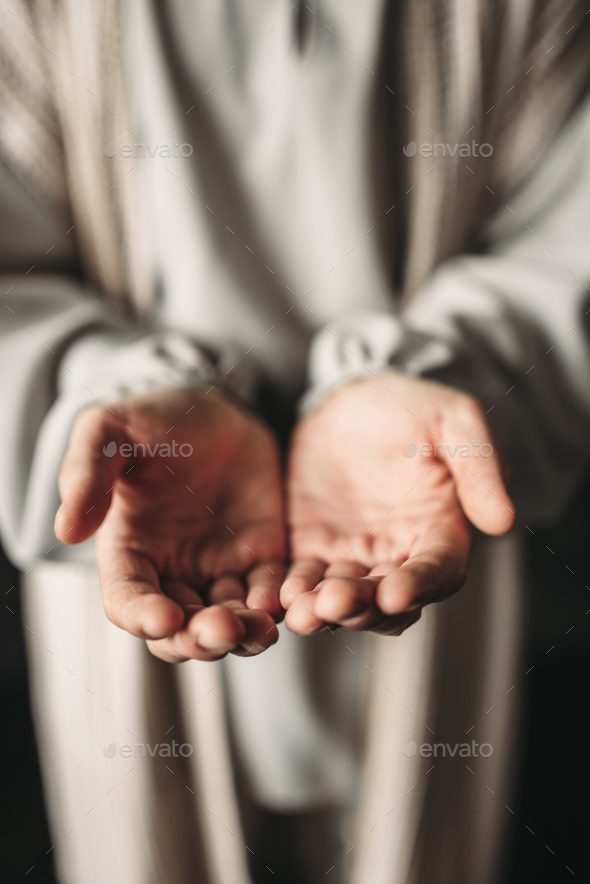 Man in white robe reaching out his hands - Stock Photo - Images