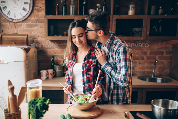 Husband kissing wife on kitchen while she cooking - Stock Photo - Images