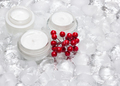 Glass jars of cream with red berries bunch surrounded by ice cub - PhotoDune Item for Sale