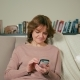 Nice Adult Woman Is Using App on Smartphone Sitting on Sofa in a Cozy Room - VideoHive Item for Sale