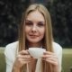 Adorable Young Woman Drinks Her Coffee Sitting in the Cafe - VideoHive Item for Sale