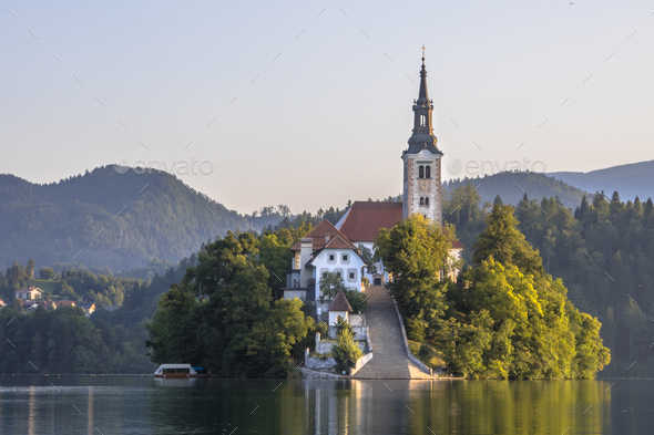 Island in lake Bled in hazy morning light - Stock Photo - Images