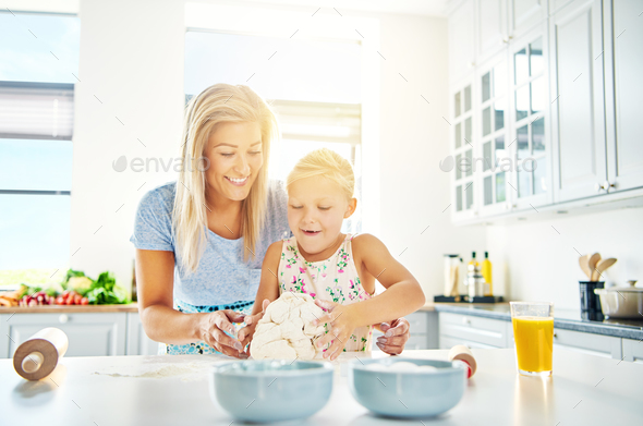 Happy child learning to bake with her mother - Stock Photo - Images