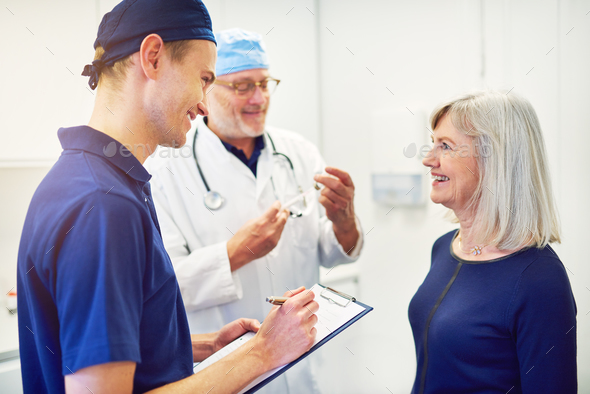 Doctor consulting woman while smiling assistant writing in tablet - Stock Photo - Images