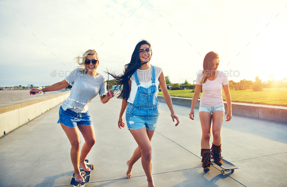 Three young woman skateboarding at the beach - Stock Photo - Images