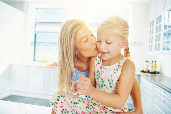 Mother kissing daughter in bright kitchen - Stock Photo - Images