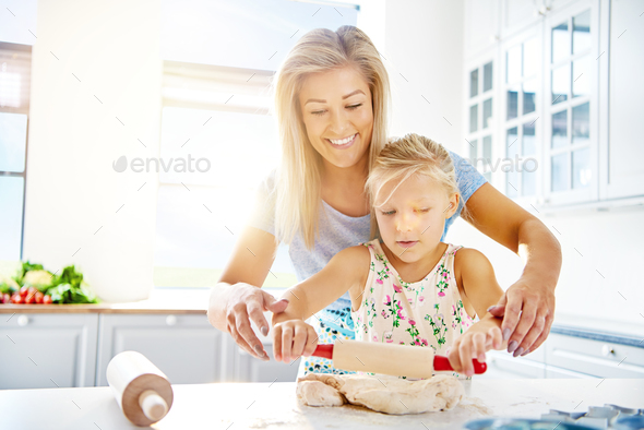 Cute little girl learning to roll out dough - Stock Photo - Images