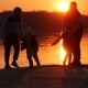 People Play on a Lake at Sunset. Silhouettes of a Little Children and Parents Time Together Next - VideoHive Item for Sale