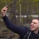 The Tourist Photographs Himself on a Mobile Phone in the Forest - VideoHive Item for Sale