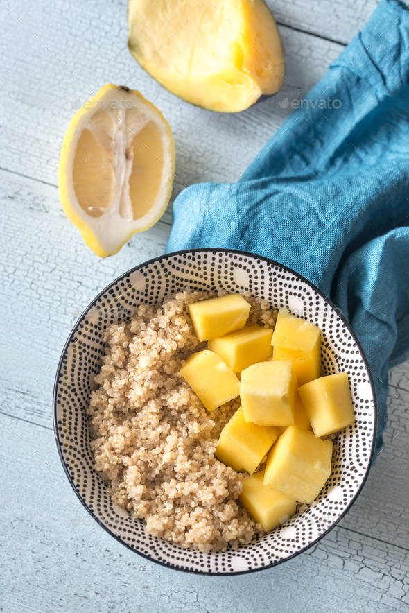 Portion of cooked quinoa with mango slices - Stock Photo - Images