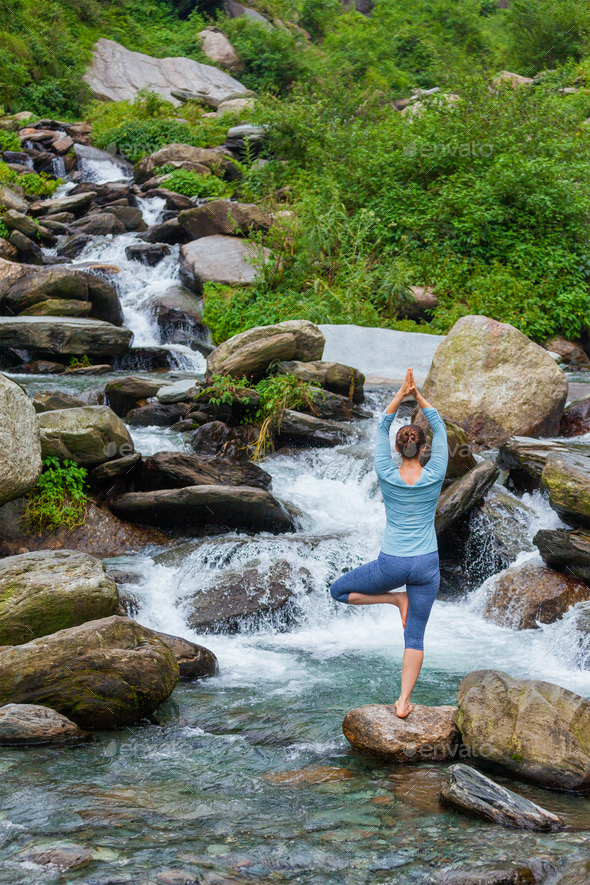 Woman in yoga asana Vrikshasana tree pose at waterfall outdoors - Stock Photo - Images