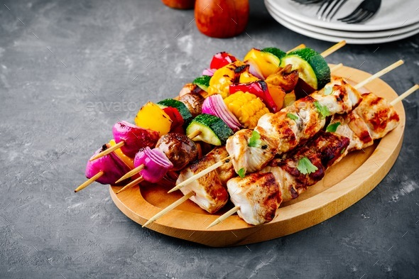 Grilled vegetable and chicken skewers with sweet corn, paprika, zucchini, onion, tomato and mushroom - Stock Photo - Images