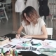 Young Fashion Designer Girl Makes a Sketch in Pencil at the Atelier. Business Woman with Asian - VideoHive Item for Sale