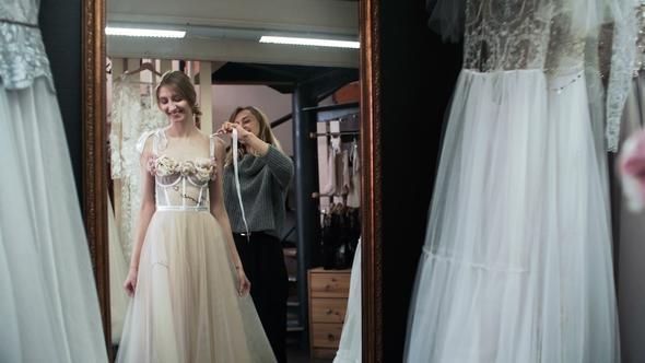 Fashion Tailor Is Helping Bride Choose Wedding Dress. Wedding Gown ...