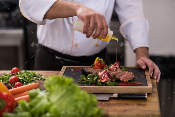 Chef finishing steak meat plate - Stock Photo - Images