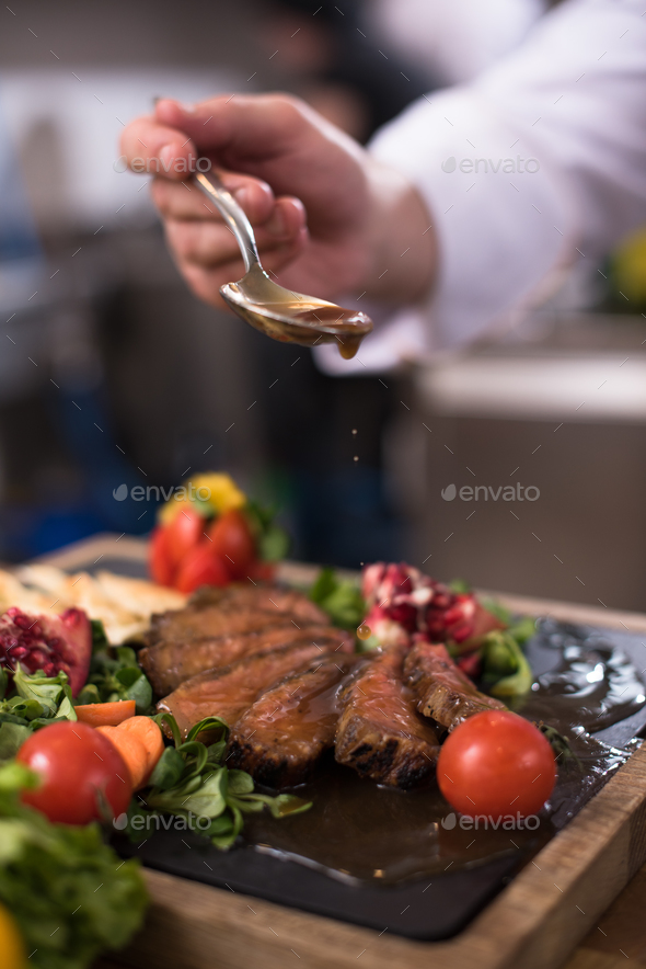 Chef hand finishing steak meat plate - Stock Photo - Images