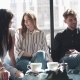 Best Friends Spend Time Together Sitting in a Cafe. Man and Two Girls Drink Coffee and Talk  - VideoHive Item for Sale