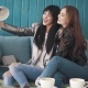 Girlfriends Do Selfie on Mobile Phone Cameras While Sitting in a Cafe - VideoHive Item for Sale