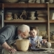 Cute Small Boy Is Playing with Clay Making Ceramic Toy in His Grandfather's Workshop. Grey-haired - VideoHive Item for Sale
