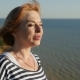Happy Woman Stands on the Black Sea Shore and Smiles in Summer - VideoHive Item for Sale