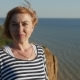 Happy Woman Stands on the Black Sea Coast and Smiles in Summer  - VideoHive Item for Sale