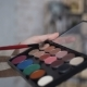 . A Palette with Eye Shadows and a Makeup Brush in Makeup Artist's Hands. The Girl Holding - VideoHive Item for Sale