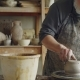 Senior Potter Working at Bottom Part of Ceramic Pot on Spinning Potter's Wheel in Workplace - VideoHive Item for Sale