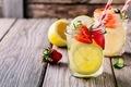 Lemon and strawberry lemonade in glass mason jars on a wooden background.