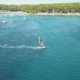 Windsurfer Gliding Across Blue Ocean Next To the Beach Resort Coastline - VideoHive Item for Sale
